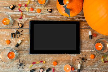 halloween pumpkins, candies, candles and tablet pc