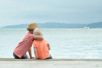 Two little brothers sit on a pier and embrace against the sea and mountains in the distance. Back view