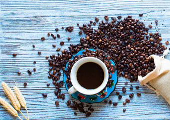 Coffee beans and cup of coffee with other components on different wooden background.  Free space for text