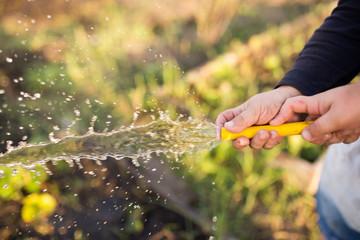 Foto op Aluminium Natuur splashing water from a hose in the garden