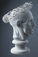 plaster statue of a human head. grey background.
