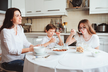 happy family having breakfast at home. Mother with two kids eating in modern white kitchen
