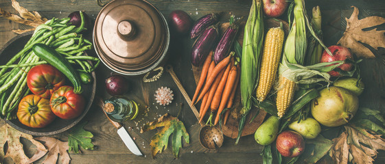 Fall healthy cooking background. Ingredients for Thanksgiving day dinner. Flat-lay of beans, corn corn, carrot, tomatoes, eggplants, fruits and fallen leaves over wooden table, top view