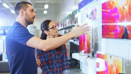 In the Electronics Store Professional Consultant Provides Expert Advice to a Young Woman Who Looks for a  New TV to Buy. In This Bright, Modern Store.