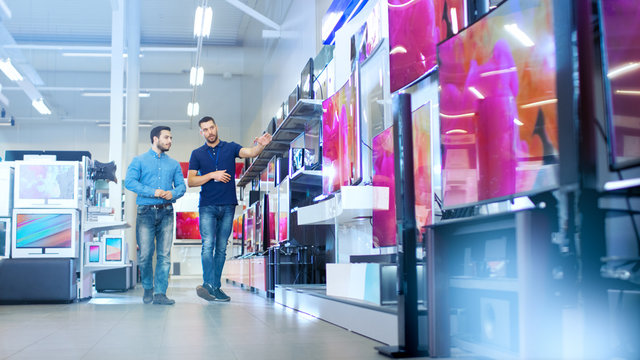 In the Electronics Store Professional Consultant Shows Latest UHD TV's to a Young Man, They Talk about Specifications and What Model is Best for Young Man's Home. Store is Bright, Modern.