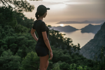 The girl stands on a hill and looks at the unleashed landscape. Seascape with a bird's-eye view at sunset