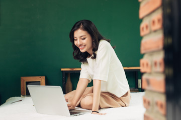 Beautiful young smiling woman working on laptop while sitting on bed