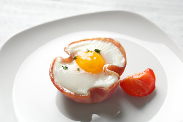 Plate with tasty egg in ham on table