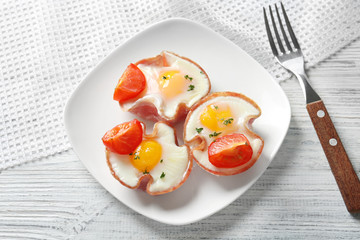 Plate with tasty eggs in ham on table