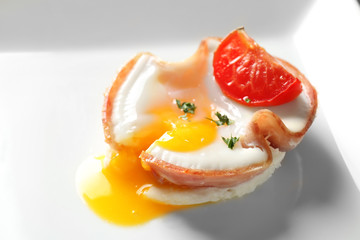 Tasty egg with tomato in ham on white plate, closeup