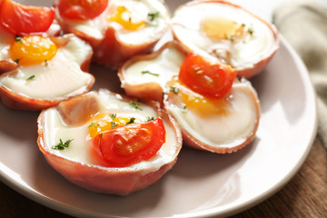 Tasty eggs with tomatoes in ham on plate, closeup