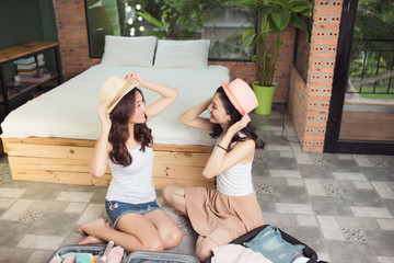 Friendship. Travel. Two asian young woman friends packing a travel bag before going on holiday