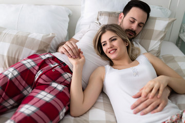 Young attractive couple having romantic time in bed