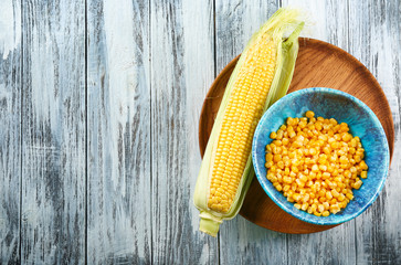 Corn cob and bowl with kernels on tray against wooden background