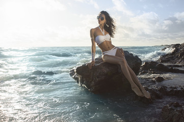 a girl in a white bathing suit sits on a rock