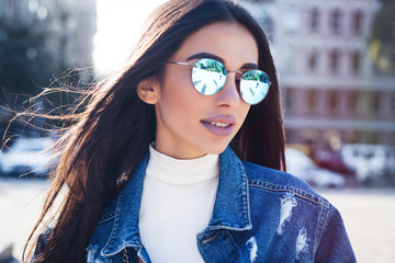 Hipster girl wearing blank gray t-shirt, jeans and backpack posing against rough street wall, minimalist urban clothing style.Attractive woman in jeans with long dark hair