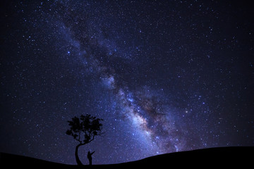 A Man is standing unter tree pointing on a bright star with milky way galaxy and space dust in the universe
