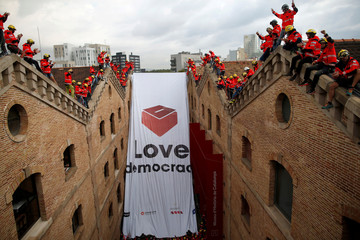 Firemen react as they hang a huge banner in favour of the banned October 1 independence referendum at the Catalonia's History Museum in Barcelona