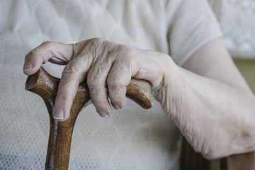 wrinkled hand of a senior person on cane