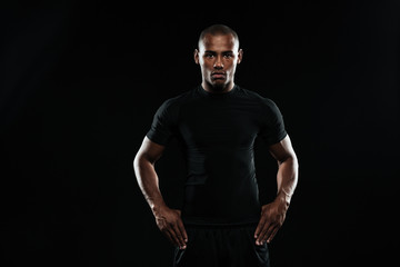 Serious afro american sports man with arms  on his hips looking at camera