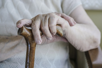 wrinkled hand of a senior woman on cane
