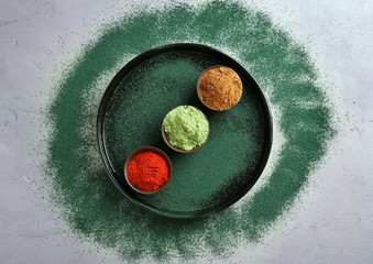 Plate with different colorful superfood powders on table