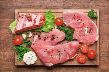 Wooden board with different types of meat on table