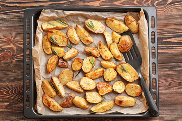 Baking tray with delicious rosemary potatoes on table