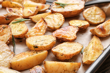 Delicious baked potatoes with rosemary on baking tray, closeup