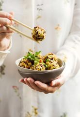 Donna caucasica che regge in una mano una scodella di polpette vegetariane e con l'altra mano impugna delle bacchette
