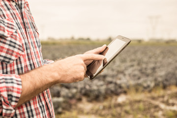 Tablet in farmer's hands, cabbage field as background