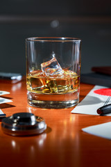 Scotch with ice on the desktop among contracts and documents