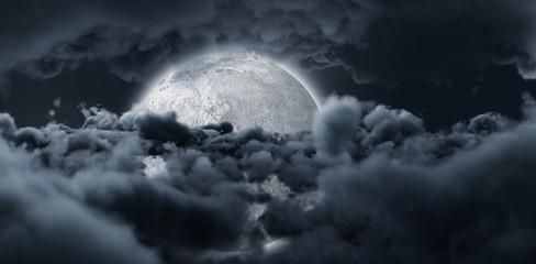 Shining moon hide by dark grey clouds in the sky
