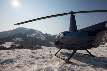 Helicopter landed on the snow in the mountains during a sunny summer day. Taken near Vancouver, BC, Canada.