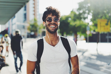 Young travel blogger is ready for a new weekend trip. Bearded backpacker is standing on a blurred station background. Student is relaxing on a weekend. Hipster guy wearing sunglasses smiling at camera