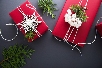 Christmas handmade gift boxes decorated with red paper, green branches and white snowflakes on dark grey background top view. Merry christmas greeting card. Winter xmas holiday theme. Happy New Year.