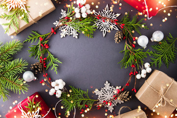 Frame with christmas wreath, gift boxes, branches and snowflakes on dark background top view. Merry christmas greeting card. Winter xmas holiday theme. Happy New Year. Flat lay. Sparkle bokeh lights.