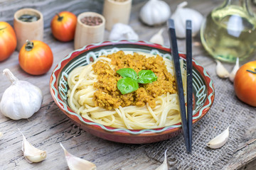 Soy vegan protein marinara spaghetti pasta in ceramic bowl with chopsticks on wooden background. Protein albumen source. Vegan vegetarian nutritional food.