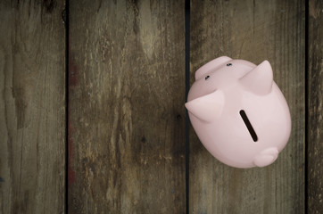 Pink piggy bank on wooden background copy space