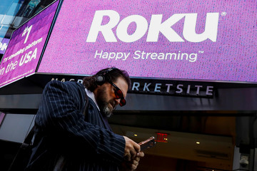 A man passes by a video sign display with the logo for Roku Inc, a Fox-backed video streaming firm, after the company's IPO at the Nasdaq Marketsite in New York