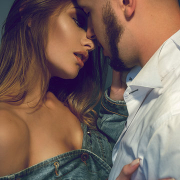 square portrait of young sensual couple in love higs and kisses