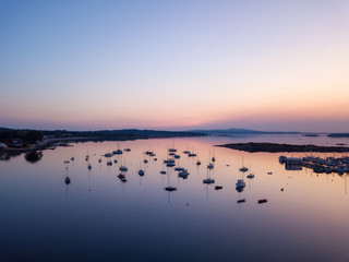 Aerial panoramic view of sail boats parked in a marina during a vibrant sunrise. Taken in Victoria, Vancouver Island, British Columbia, Canada.