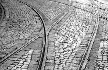 Straßenbahnschnienen kreuzen sich im Kopfsteinpflaster, Schwarzweißaufnahme