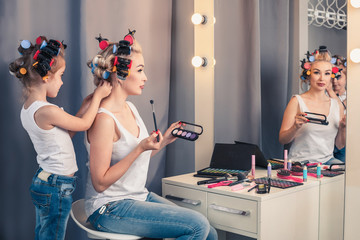 Beautiful young mother and her daughter with hair curlers are sp