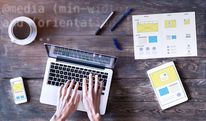 Webdesigner sketching responsive website wireframe with laptop, smartphone and tablet