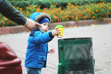 A small child in the street throws a paper glass in the trash can. His dad points with his finger where to throw garbage. The concept of a clean planet. Parents teach children purity