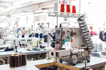 Professional sewing machine with different colors of threads in the textile factory.