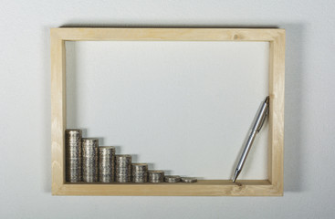 stack coin with pen in wooden frame on white wall background. Financial and saving concept.