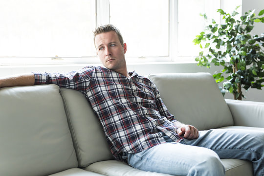 Depressed man thinking on the sofa alone at home