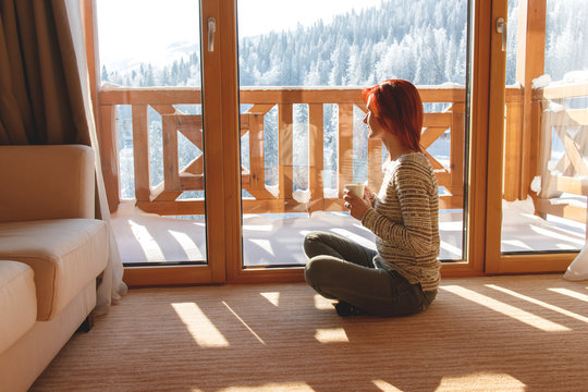 Woman sitting on floor in her home drinking coffee and looking through window at snow covered mountain. She is meditating.